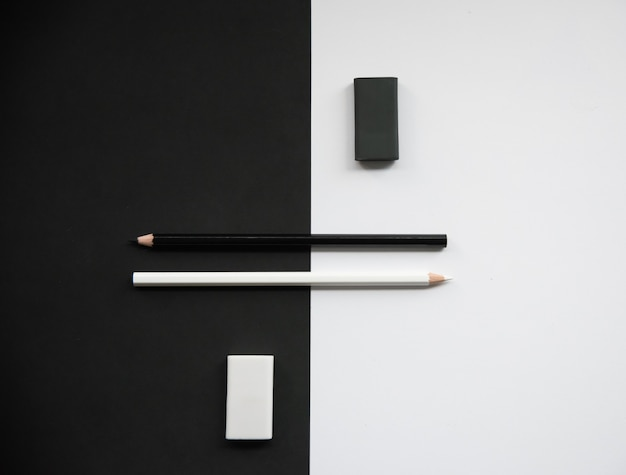 Pencils with rubber on color black and white background, top view