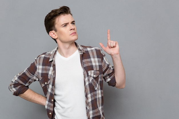 Pencive concentrated smart young man in plaid shirt having an idea and pointing up