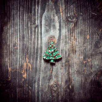 펜던트 크리스마스 트리는 오래된 나무 보드에 놓여 있습니다.