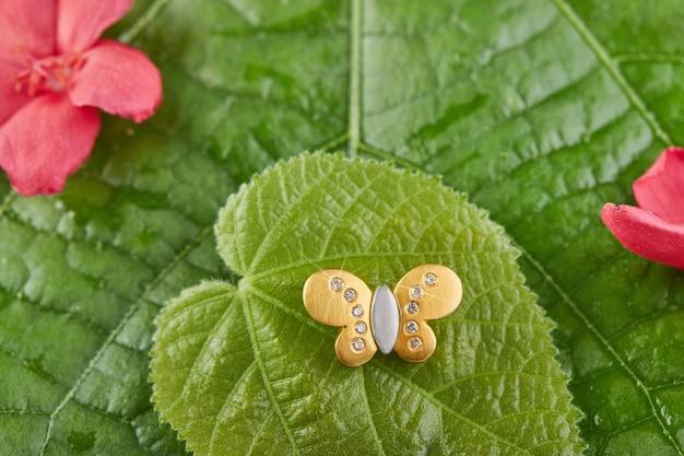 花と緑の葉の上にダイヤモンドと蝶の形をしたホワイトとイエローゴールドのペンダント。