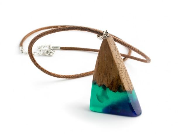青い色の白い背景で隔離のペンダント。エポキシ樹脂と木材で作られた宝石
