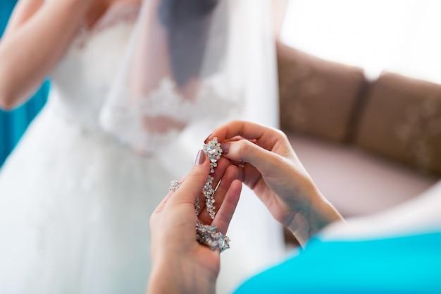 シルバーで作られたペンダントジュエリーと、花嫁のためのダイヤモンドの楕円形の女性のイヤリング。閉じる。