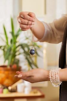 Pendulum in the hands of a reiki healer