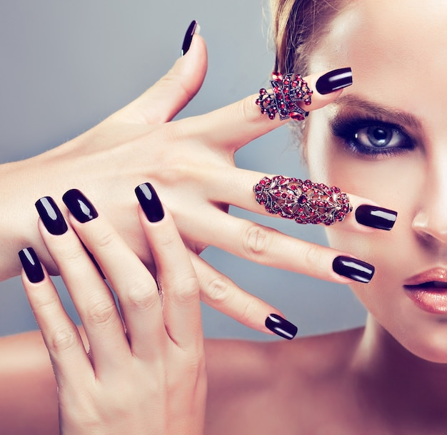 Penetrating look of woman eye painted in black smoky eyes style makeup. bold gesture slender fingers demonstrating black manicure on the nails. cosmetics, makeup and manicure.