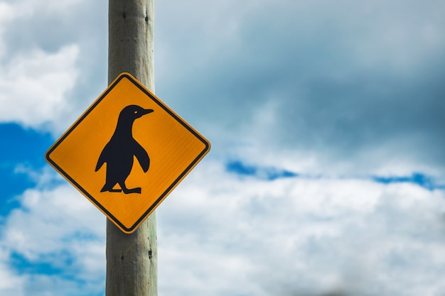 Penguins crossing sign with cloudy sky in otago, new zealand