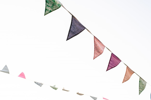 Pennants with blue sky background and pale colors hanging on a rope crossing the image