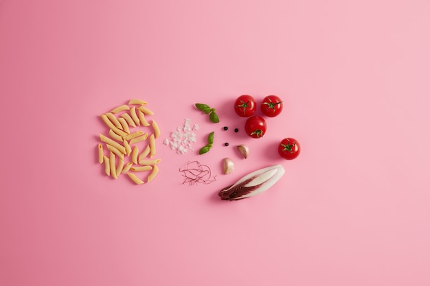 Penne dry rice pasta basil, chicory salad, tomatoes, garlic red chili pepper threads for preparing delicious gourmet italian cuisine. uncooked macaroni and ingredients on rosy background. healthy food