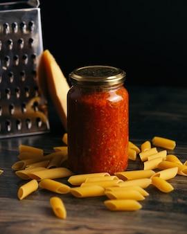 ペンネパスタとチーズとおろし金を背景にしたテーブルの上のソースの瓶