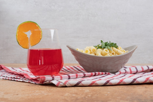 ペンネパスタとテーブルクロスの上の赤いカクテルのグラス