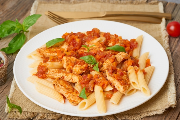 Penne pasta, chicken or turkey fillet, tomato sauce with a basil leaves on old rustic wooden