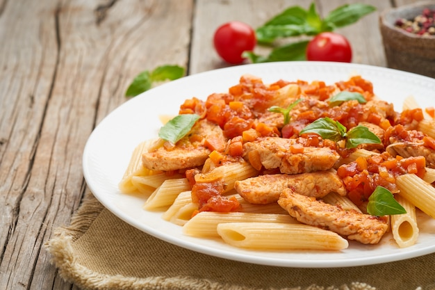 Penne pasta, chicken or turkey fillet, tomato sauce with basil leaves on old rustic wooden