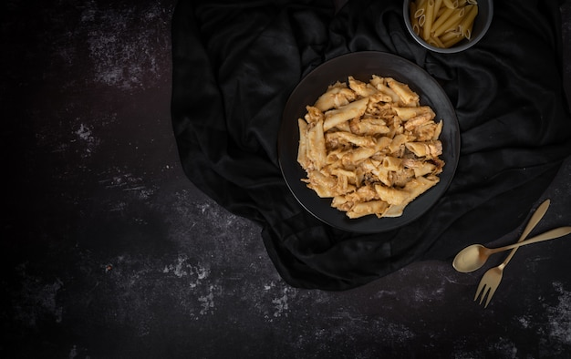 Penne pasta in a dark background with a space for text or messages