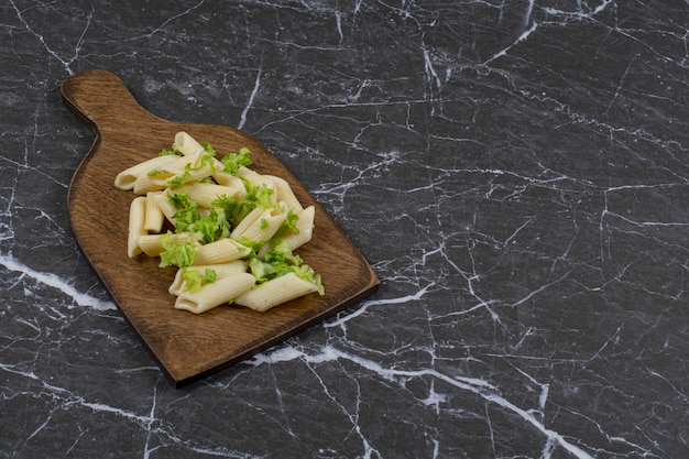 Penne pasta green vegetable sauce on wooden cutting board.