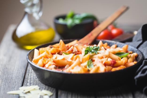 토마토 소스와 치즈의 펜네 파스타는 나무에 바질로 장식