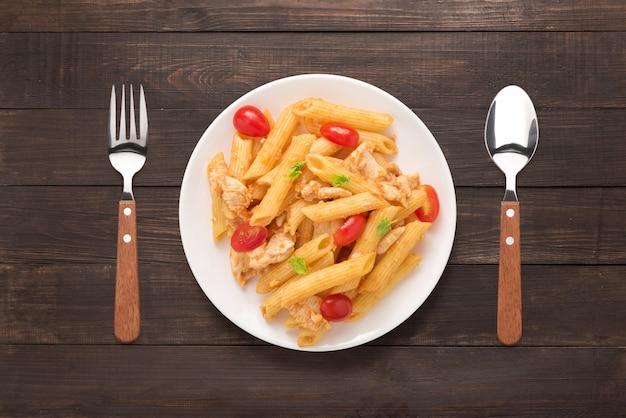 木製の背景にチキンとトマトソースのペンネパスタ