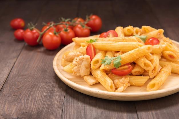 木製のテーブルにチキンとトマトソースのペンネパスタ