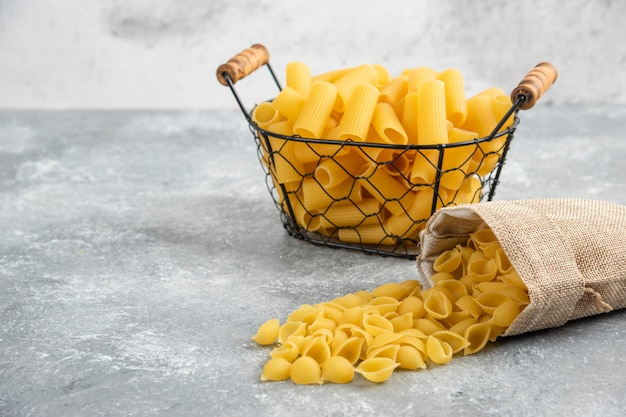 Penne pasta in a metallic container on grey marble table.