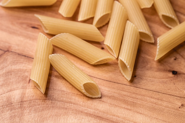 Penne pasta raw on wooden object with top view