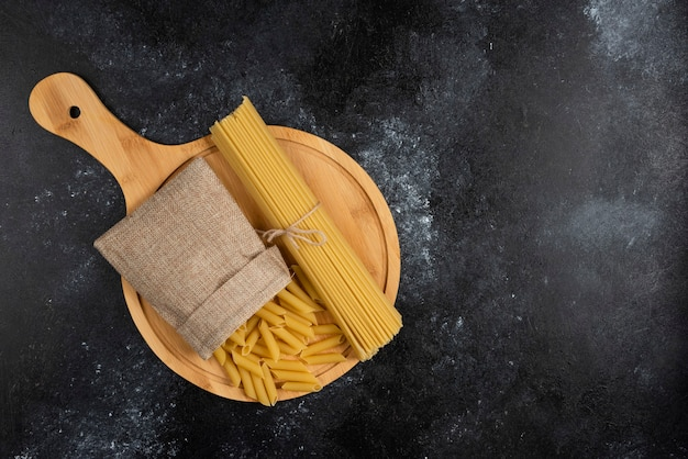 Penne pasta in a rustic basket with spaghetties on a wooden platter.