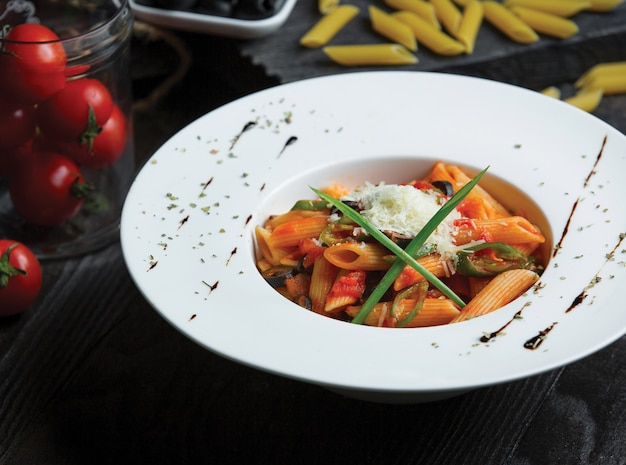 Penne pasta in tomato sauce served with herbs and parmesan