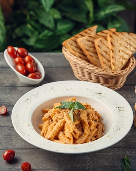 Penne pasta in tomato sauce served with toast bread.