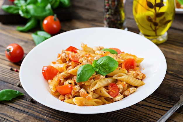 Penne pasta in tomato sauce with chicken, tomatoes, decorated with basil