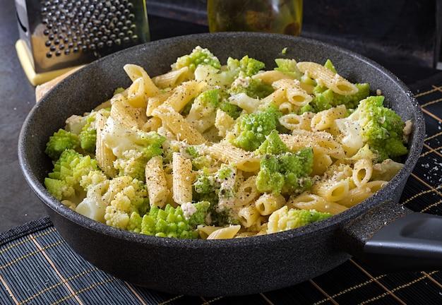 Penne pasta with cabbage romanesco on black table. vegetarian food. italian menu.