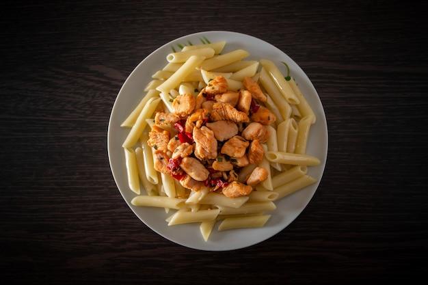 토마토 소스에 닭고기와 야채를 곁들인 펜네 파스타. 펜네 파스타와 프라이드 치킨 한 접시