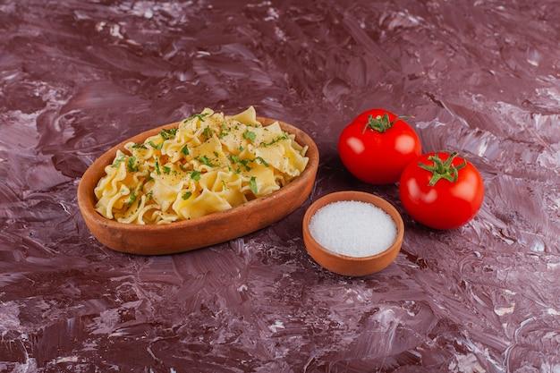 Паста пенне с майонезом и свежими красными помидорами на светлом столе.