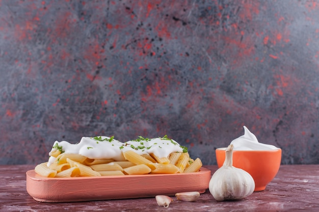 Penne pasta with mayonnaise and fresh garlic on a light table.