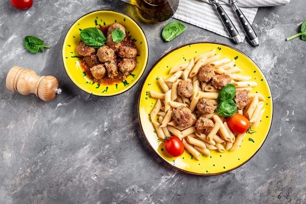 黄色いプレートと灰色の表面にミートボールとトマトソースのペンネパスタ、イタリアンパスタ
