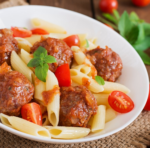 Penne pasta with meatballs in tomato sauce in a white bowl