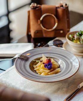 Penne pasta with parmesan in a ceramic plate in a luxury restaurant