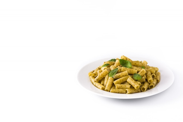 Penne pasta with pesto sauce and basil on a plate isolated on white surface. copy space