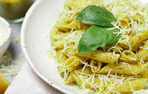 Penne pasta with pesto sauce, parmesan cheese, olive oil and basil