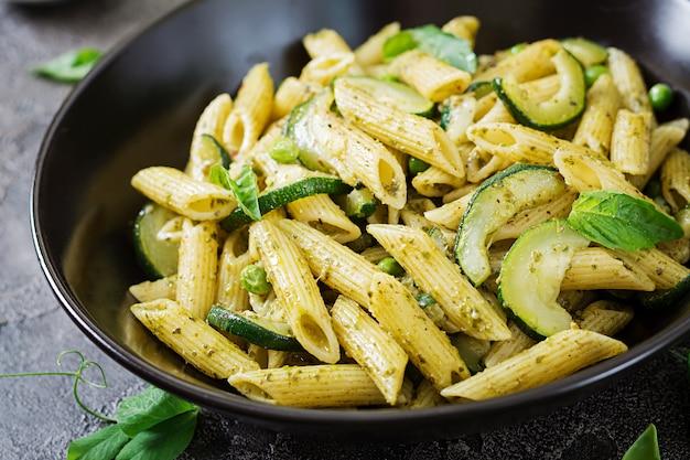 ペストソース、ズッキーニ、グリーンピース、バジルのペンネパスタ。イタリア料理。