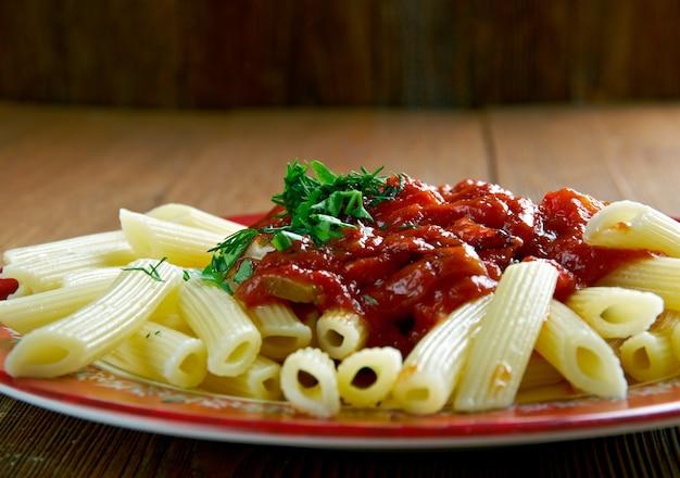 Паста пенне с соусом аррабиата. острый соус для пасты из чеснока, помидоров и красного перца чили, приготовленных на оливковом масле