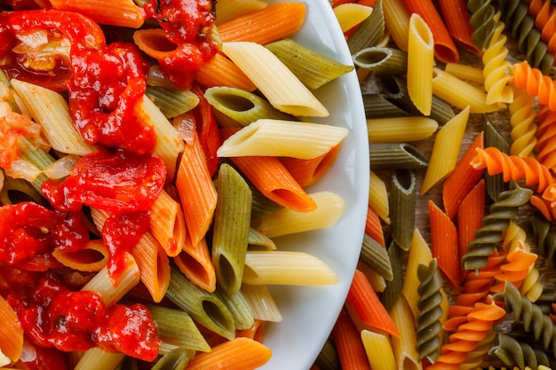Penne pasta with sauce, tomato in a plate on scattered pasta