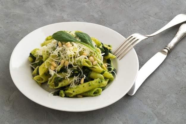 Penne pasta with spinach on grey background.