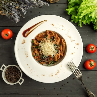 Penne pasta with tomato sauce, beef and grated cheese