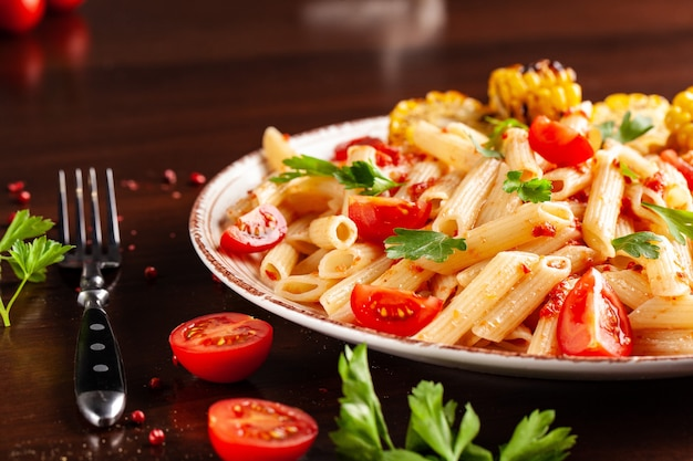 Penne pasta with tomato sauce and tomatoes.
