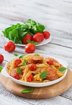木製のテーブルにフライパンで飾られたソーセージ、トマト、グリーンバジルのトマトソースのペンネパスタ