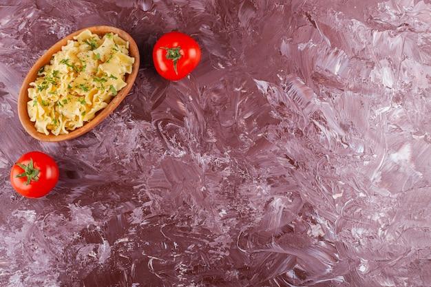 Pasta di penne con due pomodori rossi freschi su un tavolo luminoso.