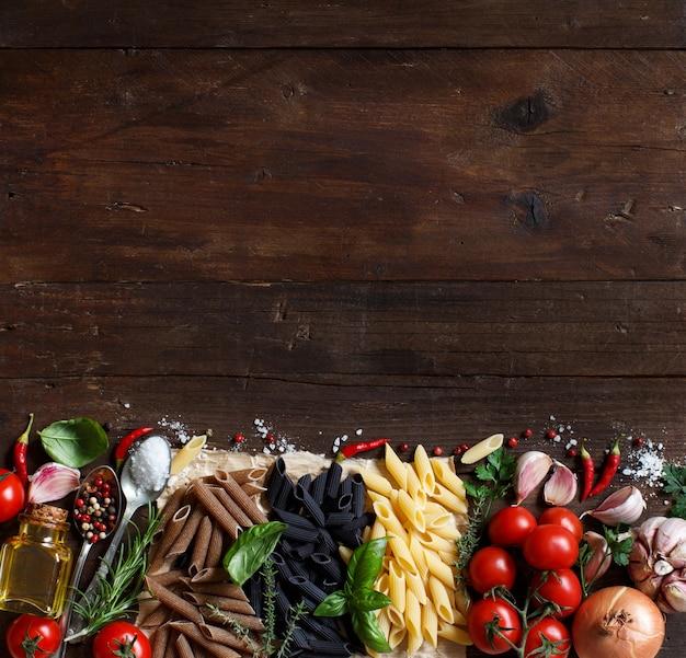 Паста пенне с овощами, зеленью и оливковым маслом на деревянном столе