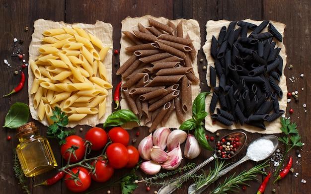 木製のテーブルに野菜、ハーブ、オリーブオイルのペンネパスタ