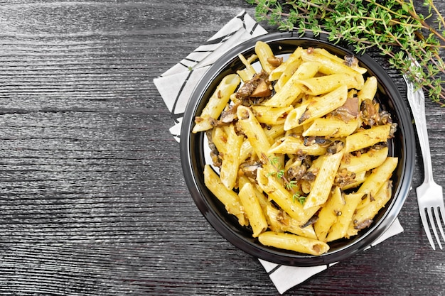 Penne pasta with wild mushrooms in a plate on a kitchen towel, thyme, fork and garlic on black wooden board background from above