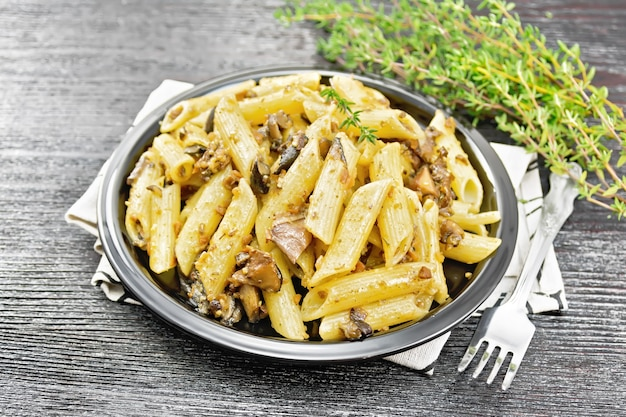 Penne pasta with wild mushrooms in a plate on a towel, thyme, fork and garlic on a wooden board background