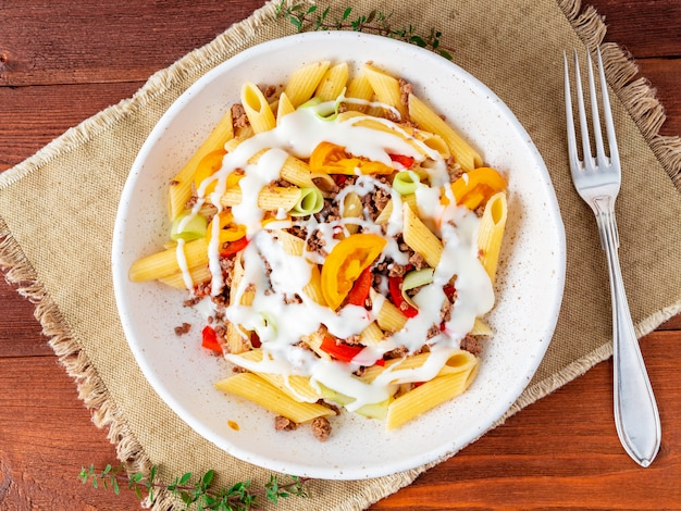 Penne pasta with yellow tomatoes, vegetables, mincemeat, white sauce