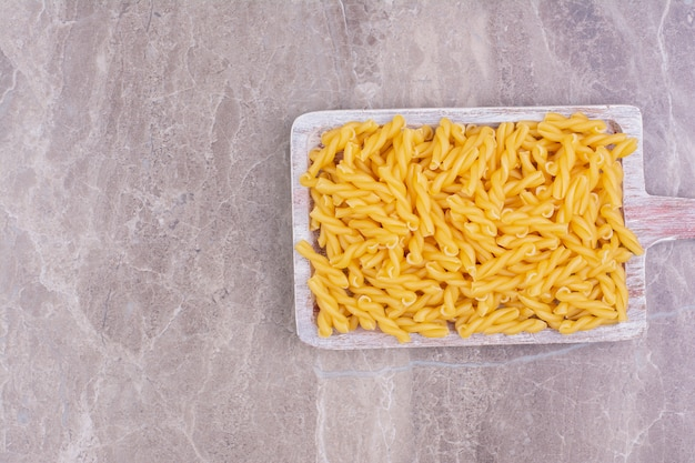 Penne pastas on a blue rustic wooden platter.