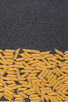 Penne rigate on gray background. raw pasta background. vertical frame